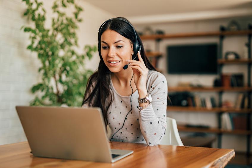 Une femme travaille dans son salon avec un casque et un micro sur son ordinateur